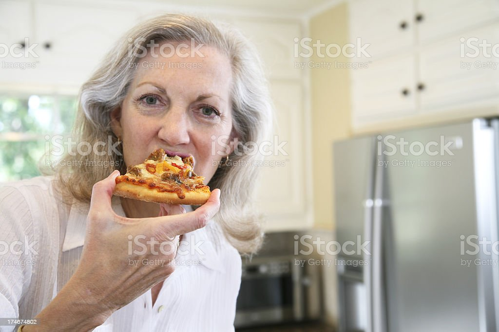 Senior Adult Woman in Kitchen Eating a Pizza stock photo