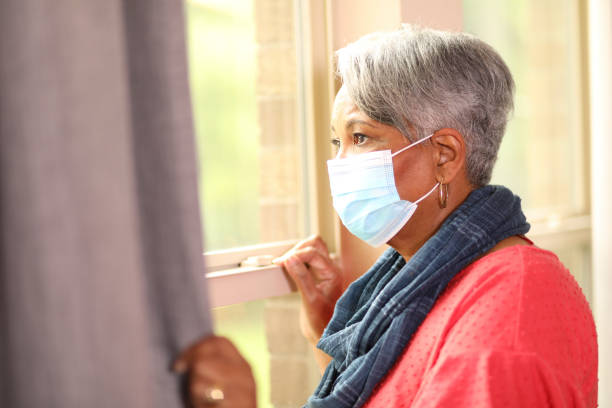 Senior adult woman looks out home window, sunny day, mask. African descent, senior adult woman looks out her window on a sunny summer day.  She wears a protective mask to protect herself from COVID-19. covid-19 stock pictures, royalty-free photos & images
