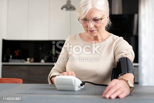 Senior adult woman measuring blood pressure at home