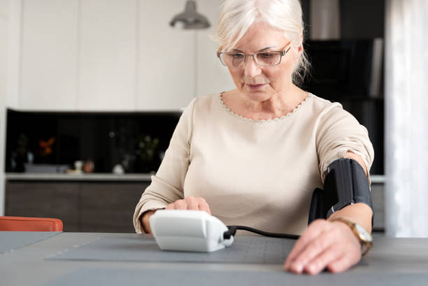 Senior adult woman measuring blood pressure stock photo