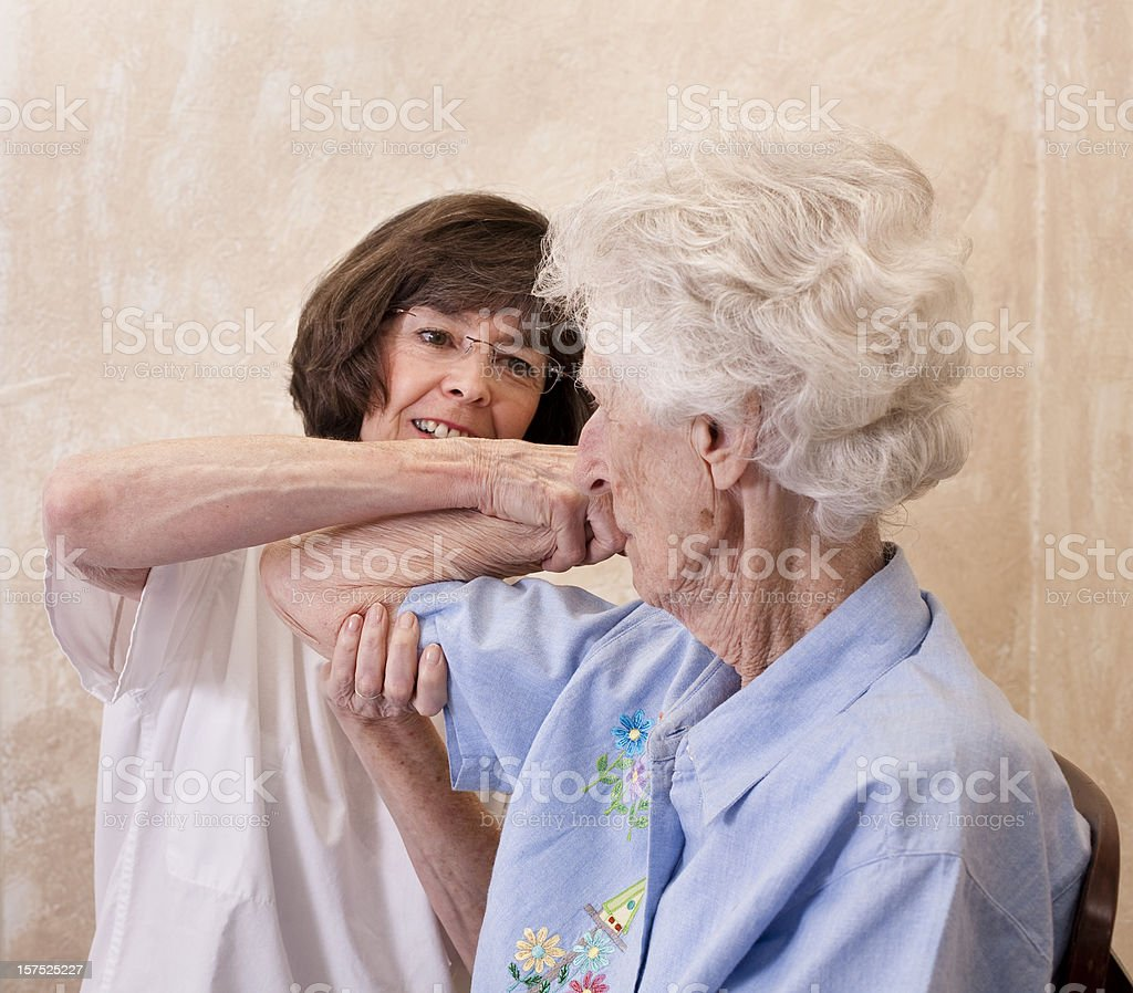 Senior adult woman, physical therapy on arm. Nurse, doctor, therapist. royalty-free stock photo