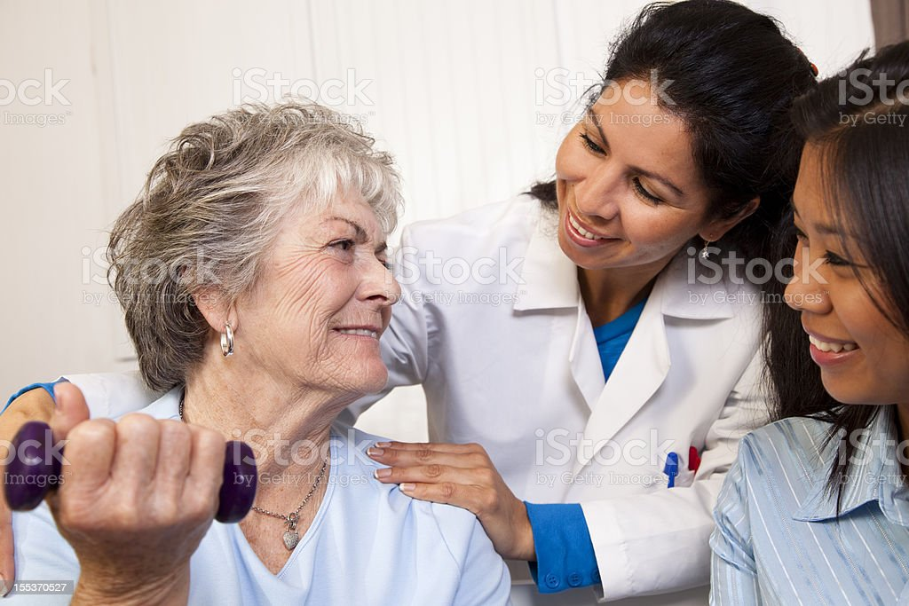 Senior adult woman, physical therapy. Therapist, doctor, nurse. Healthcare. Home. royalty-free stock photo