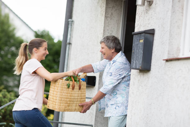 Senior adult woman receives groceries at home from young caregiver stock photo