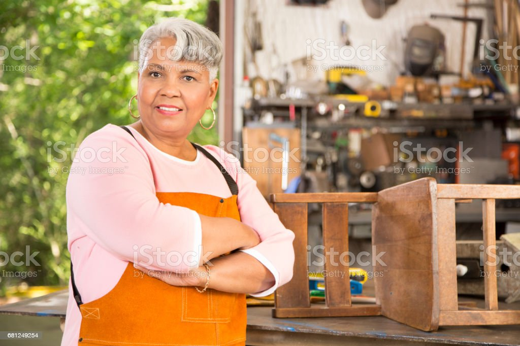 Senior adult woman restores antique furniture in workshop. royalty-free stock photo
