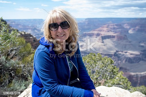 Senior adult woman (60s) sits and poses at a viewpoint along the South Rim of the Grand Canyon National Park while on vacation