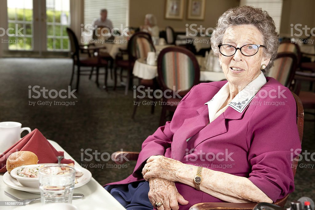 Senior Adult Woman Sitting at Dinner Table in Dining Hall royalty-free stock photo