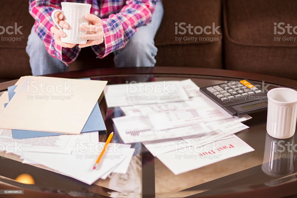 Senior adult woman struggles to pay past due bills. Home. stock photo