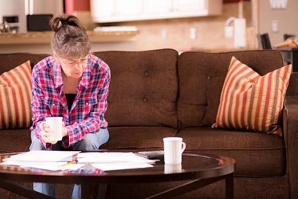 senior mujer adulta justicia a pagar facturas atrasados. su hogar lejos del hogar. - embargo hipotecario fotografías e imágenes de stock