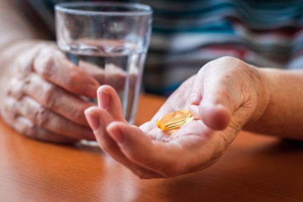 senior adult woman taking fish oil capsule. - vitamin d стоковые фото и изображения