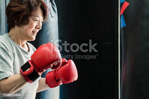 istock Senior adult woman training at boxing gym 1040320404