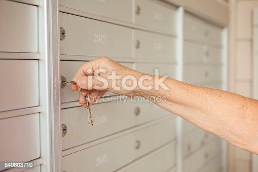 480197395istockphoto Senior adult woman using key to open apartment mailbox. 540603710