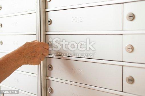 480197395istockphoto Senior adult woman using key to open apartment mailbox. 540717146