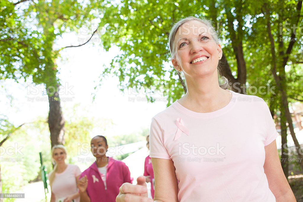 Senior adult woman walking in a breast cancer awareness race stock photo
