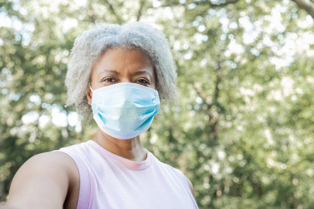 Senior adult woman wearing a mask holds camera and takes a selfie photo stock photo