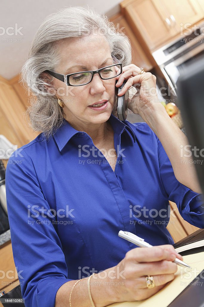 Senior adult woman working on phone and laptop in kitchen royalty-free stock photo