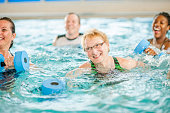 A multi-ethnic group of senior adults are taking a water aerobics class at the public pool.