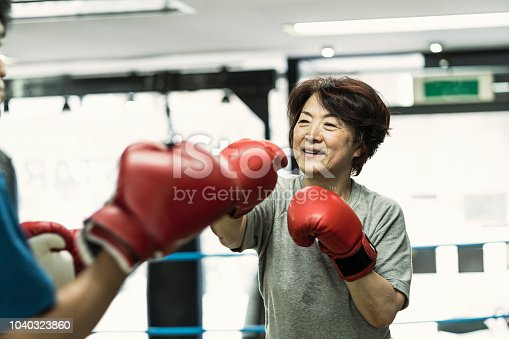 Japanese senior adult women training with male instructor at boxing gym