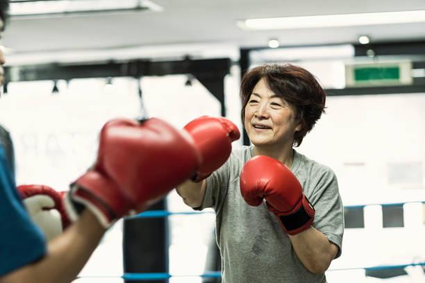 frauen in führungspositionen erwachsenen training mit männlichen lehrer an box-gym - boxen live stock-fotos und bilder