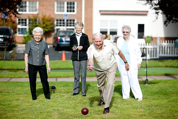 Senior adults Seniors at a retirement center having fun outside. retirement community stock pictures, royalty-free photos & images