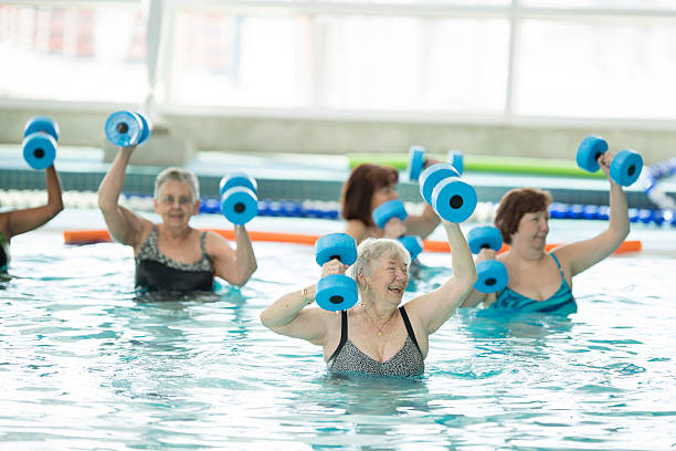 Senior Adults Taking a Water Aerobics Class at the Pool - foto stock