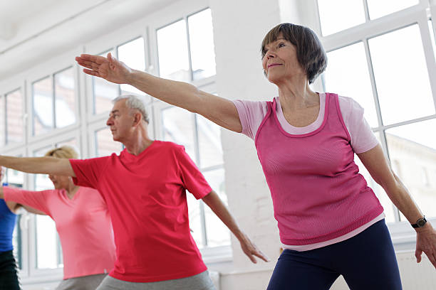 Senior adults with arms outstretched in yoga pose