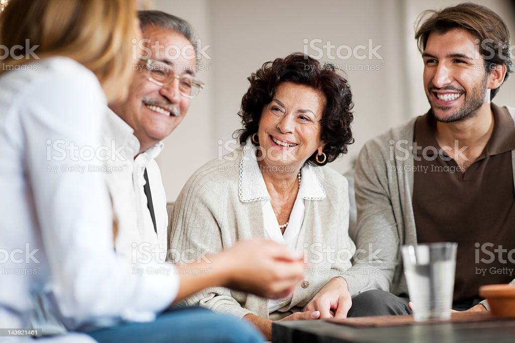 Senior adults with their adult children sitting and communicating royalty-free stock photo