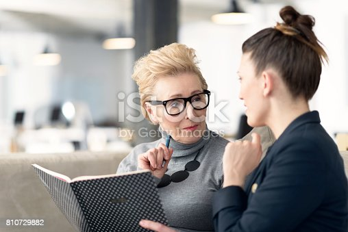 istock Senior adviser talking with young businesswoman 810729882
