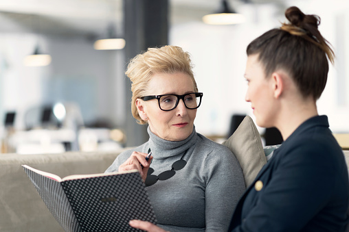 Senior Adviser Talking With Young Businesswoman Stock Photo - Download Image Now