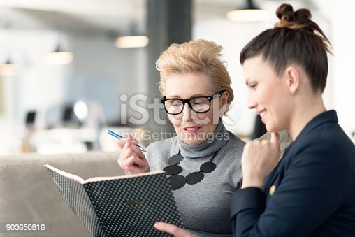 istock Senior adviser talking with young businesswoman 903650816