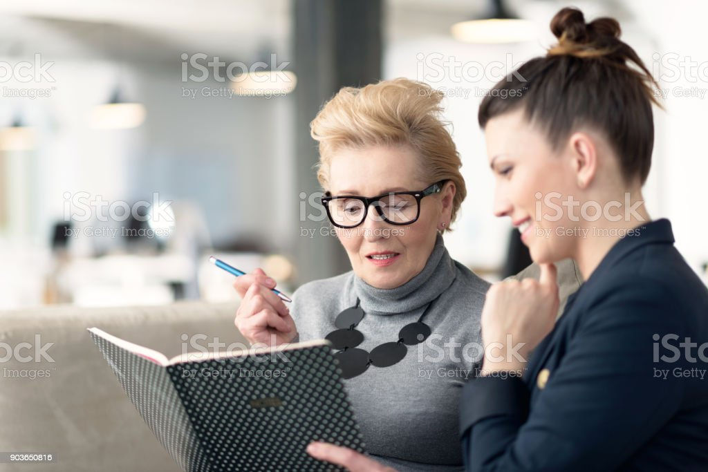 Senior adviser talking with young businesswoman stock photo