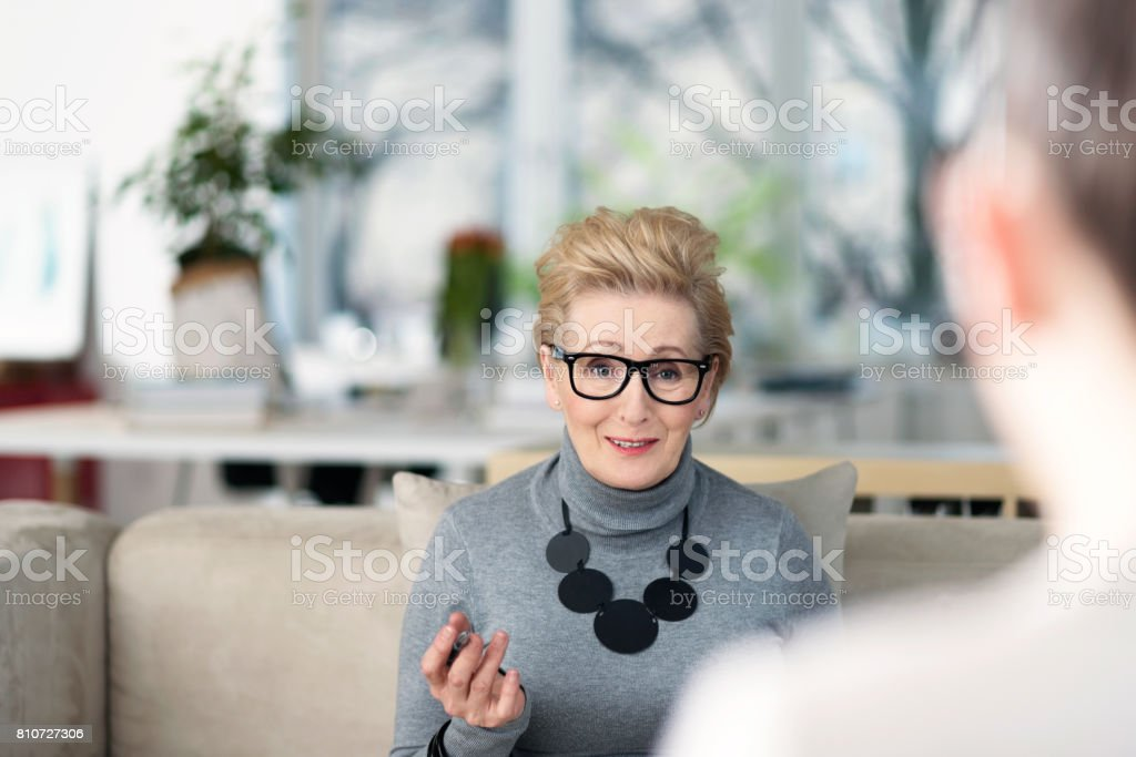 Senior adviser talking with young woman Senior woman talking with young businesswoman in an office, giving advices. 60-69 Years Stock Photo