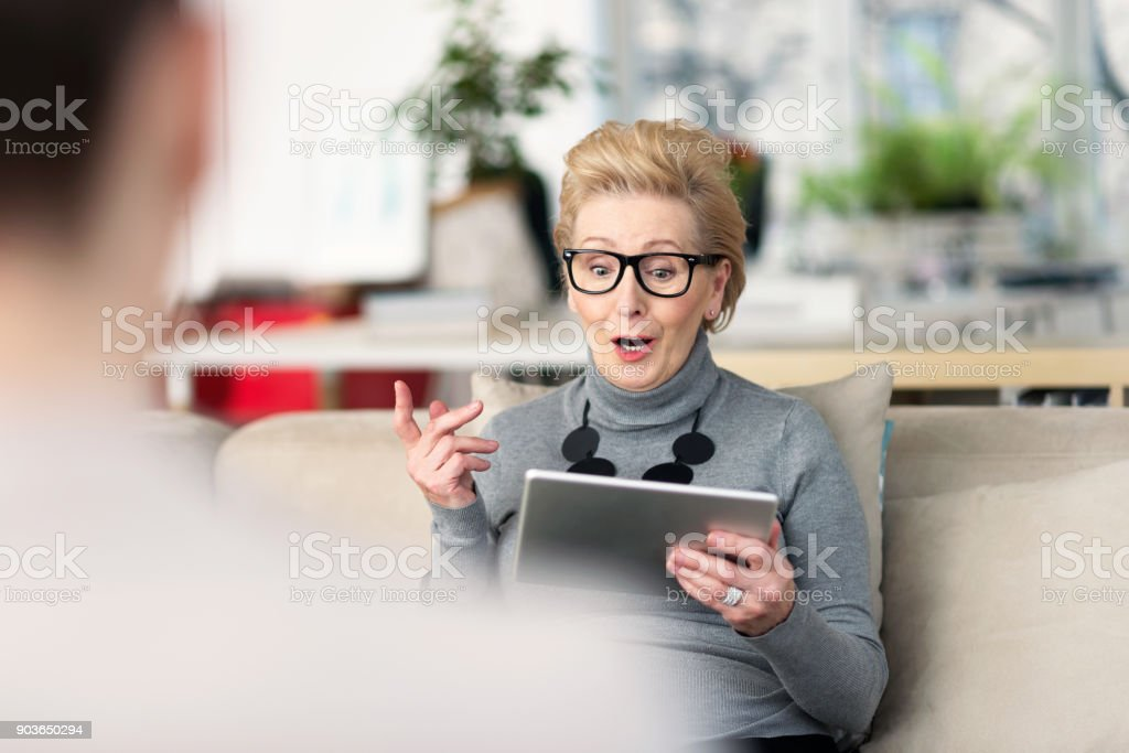 Senior adviser talking with young woman Senior woman talking with young businesswoman, giving advices, holding a digital tablet in hand. 60-69 Years Stock Photo