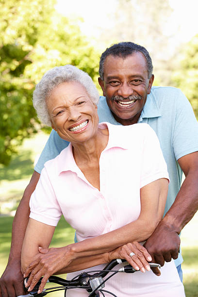 Senior African American Couple Cycling In Park stock photo