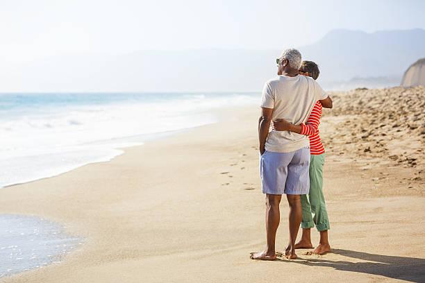 Senior African American couple embracing on beach stock photo
