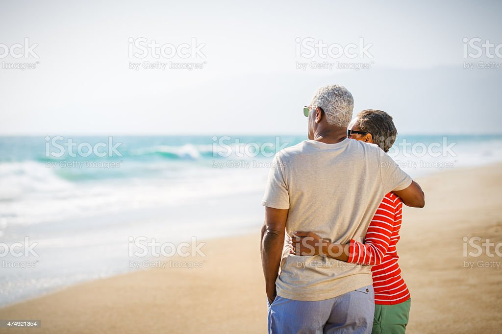 Senior African American couple embracing on beach stock photo