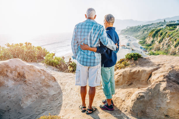 Senior African American couple embracing on rock over beach stock photo