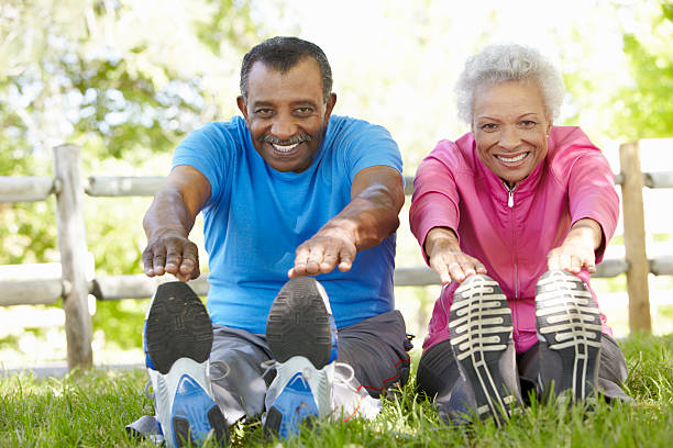 Senior African American Couple Exercising In Park  touching toes stock pictures, royalty-free photos & images