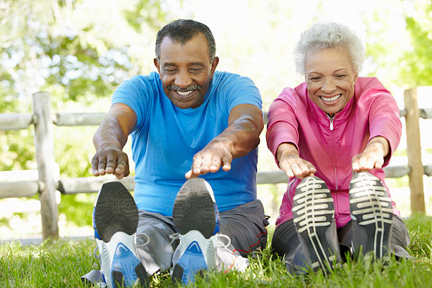 Senior African American Couple Exercising In Park Senior African American Couple Exercising In Park Stretching To Touch Toes touching toes stock pictures, royalty-free photos & images