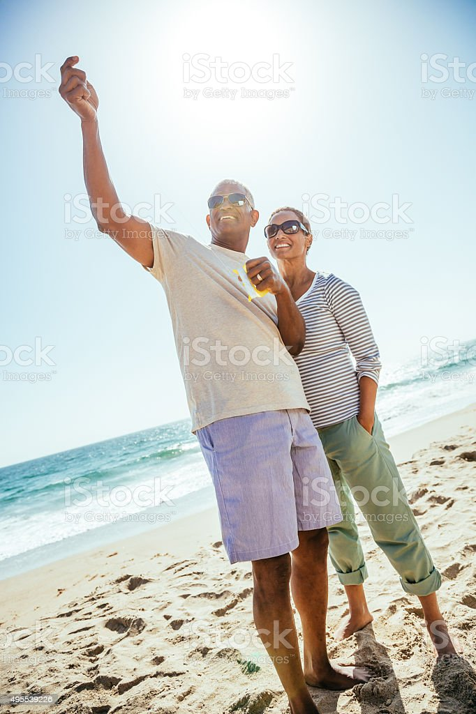 Senior African American couple flying kite on beach stock photo