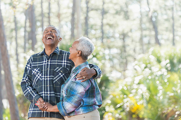 Senior African American couple holding hands in park stock photo