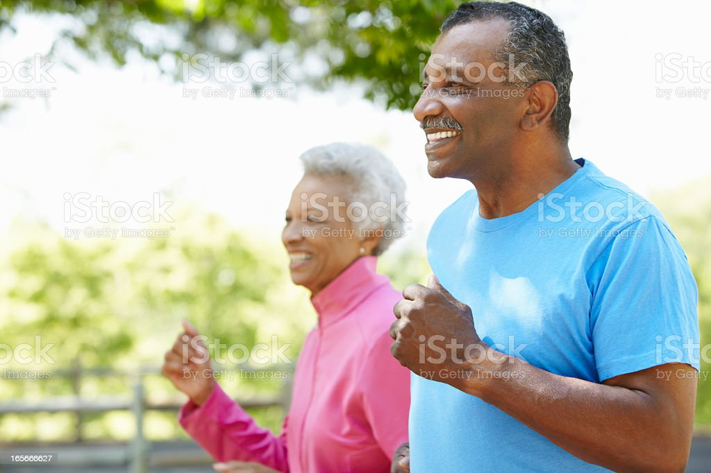 Senior African American Couple Jogging In Park stock photo