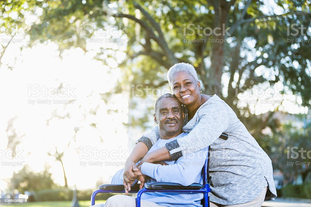 Senior African American couple, man in wheelchair stock photo
