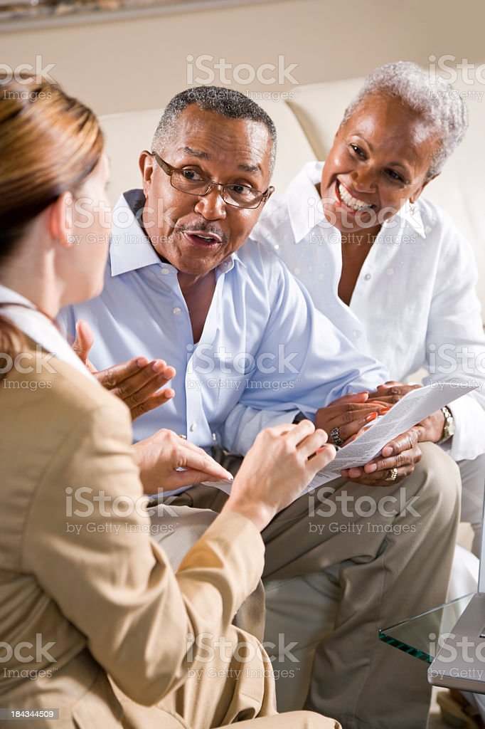 Senior African American couple meeting with female financial adv stock photo