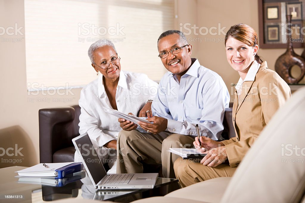 Senior African American couple meeting with financial adviser stock photo