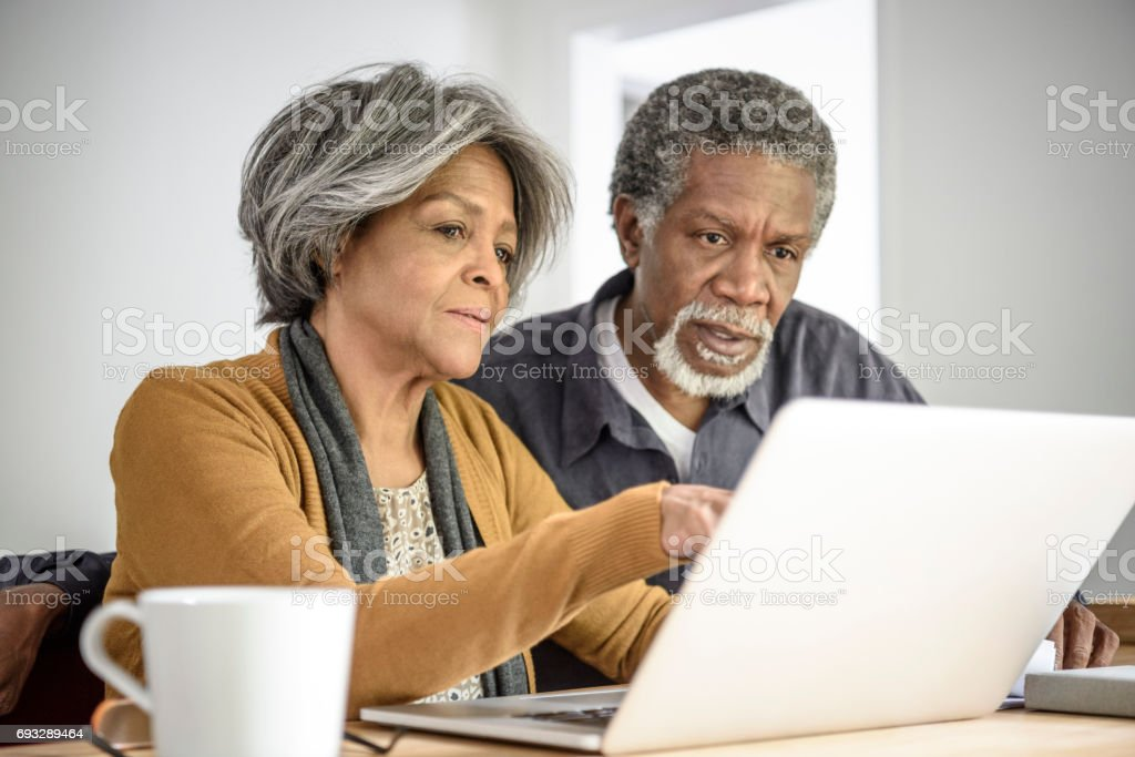 Senior African American couple on laptop together with serious expression stock photo