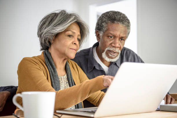 senior african american couple on laptop together with serious expression - 60 69 years stock photos and pictures