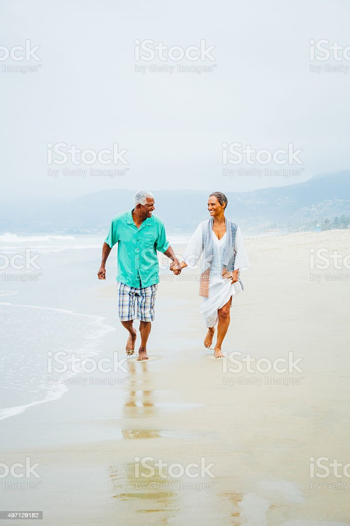 Senior African American couple on sandy beach stock photo