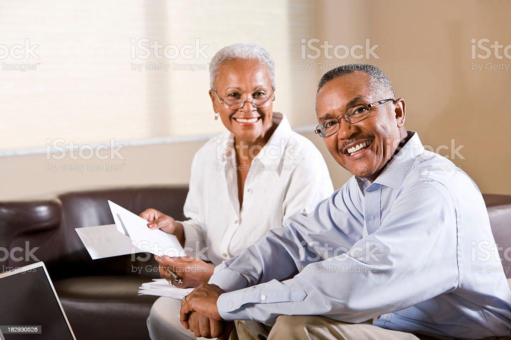 Senior African American couple paying bills online stock photo