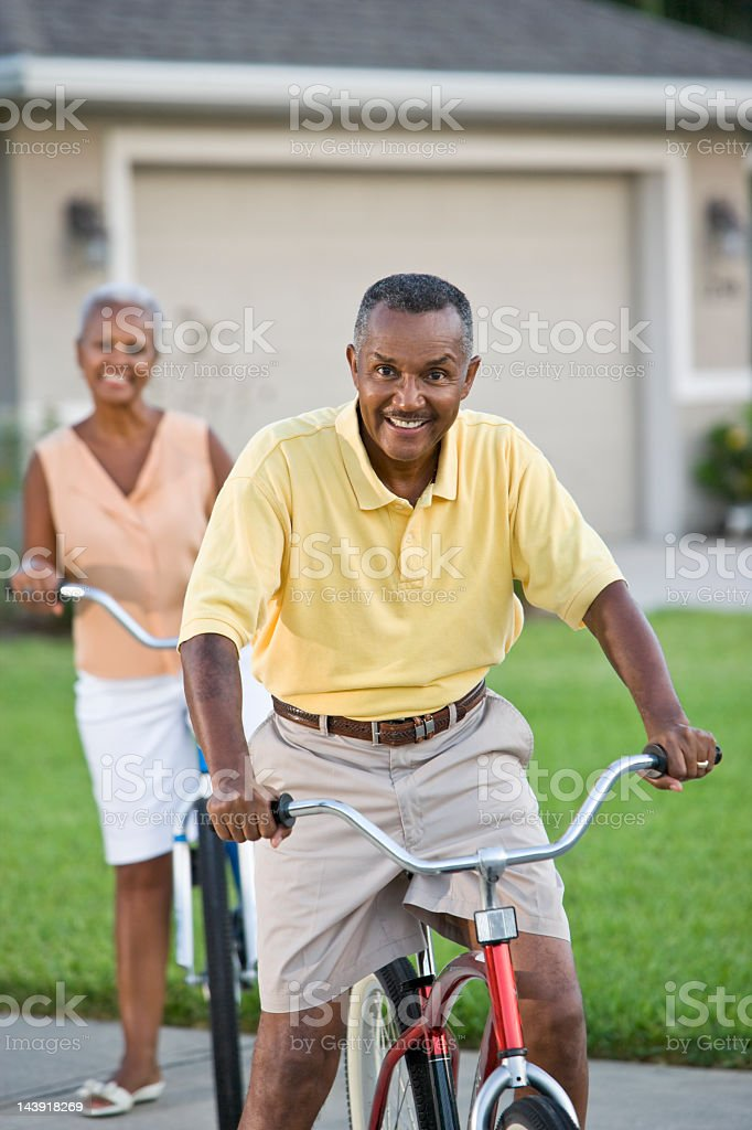 Senior African American couple riding bicycles, focus on man stock photo