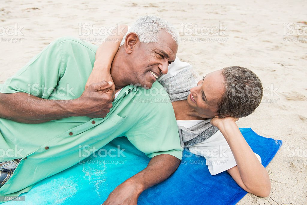 Senior African American Couple Sharing Romantic Moment on Beach stock photo
